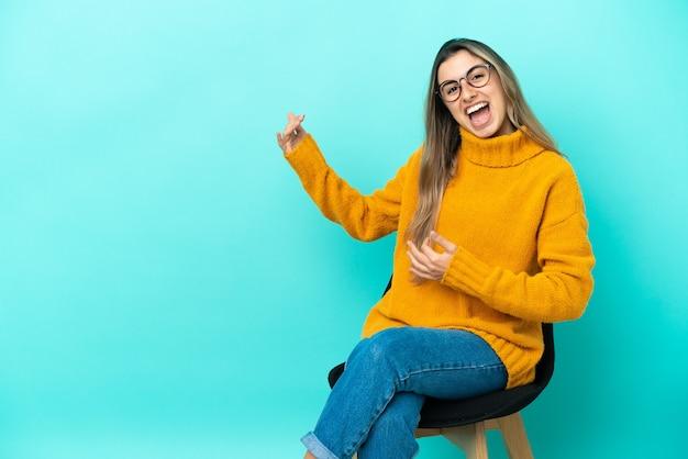 ギターのジェスチャーを作る青い背景で隔離の椅子に座っている若い白人女性