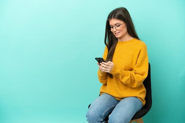 Молодая кавказская женщина сидит на стуле, изолированном на синем фоне, отправляет сообщение с мобильного телефона