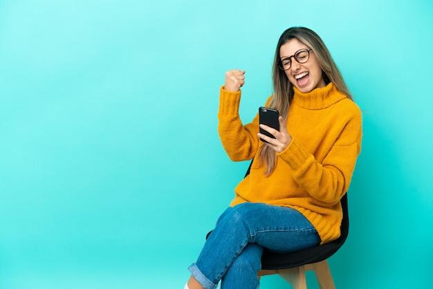 Молодая кавказская женщина сидит на стуле, изолированном на синем фоне с телефоном в позиции победы