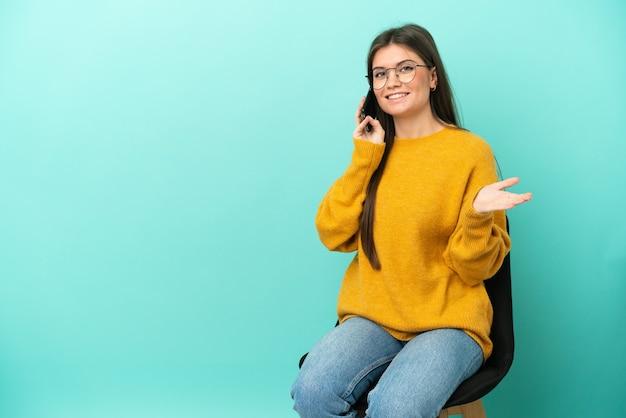Молодая кавказская женщина сидит на стуле, изолированном на синей стене, разговаривает с кем-то по мобильному телефону