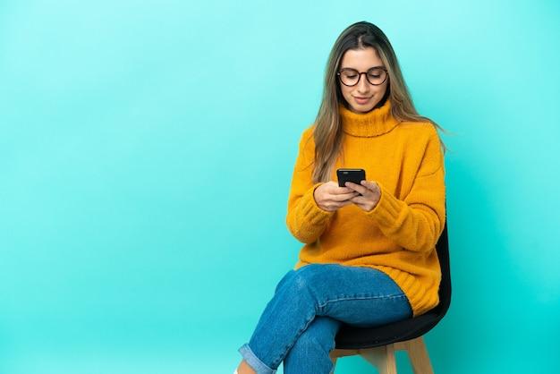 Молодая кавказская женщина сидит на стуле, изолированном на синей стене, отправляет сообщение с мобильного телефона