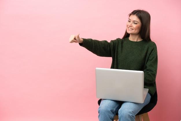 Молодая кавказская женщина сидит на стуле со своим ноутбуком, изолированным на розовом фоне, показывает палец вверх