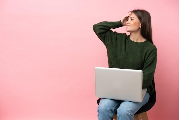 Молодая кавказская женщина, сидящая на стуле со своим ноутбуком, изолированным на розовом фоне, кое-что поняла и намеревается найти решение