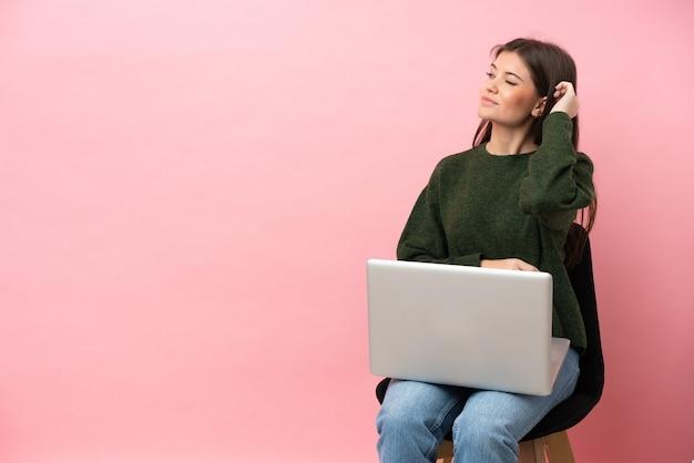 Молодая кавказская женщина сидит на стуле со своим ноутбуком, изолированным на розовом фоне, сомневается и с смущенным выражением лица