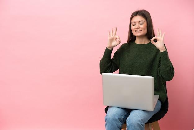 Молодая кавказская женщина сидит на стуле со своим ноутбуком, изолированным на розовом фоне в позе дзен