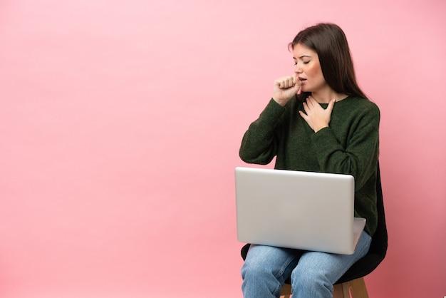 분홍색 배경에 격리된 노트북을 들고 의자에 앉아 있는 젊은 백인 여성은 기침을 하고 기분이 나쁩니다