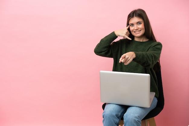 Молодая кавказская женщина сидит на стуле со своим ноутбуком, изолированным на розовом фоне, делая жест телефона и указывая вперед