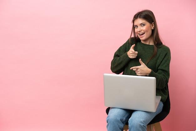 ピンクの背景に分離された彼女のラップトップで椅子に座っている若い白人女性が正面を指して笑