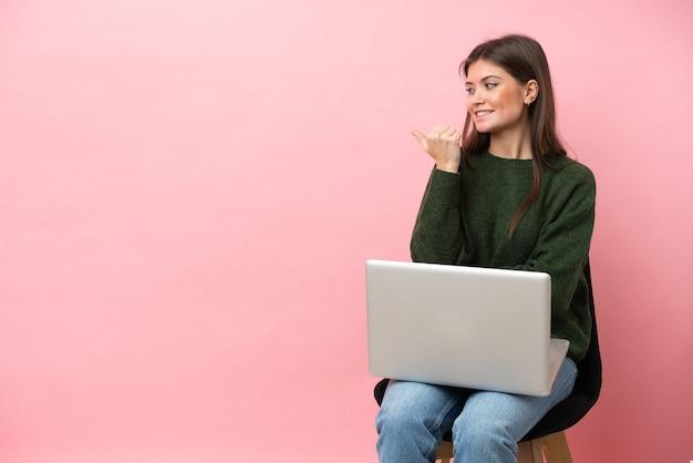 Молодая кавказская женщина сидит на стуле со своим ноутбуком, изолированным на розовом фоне, указывая в сторону, чтобы представить продукт