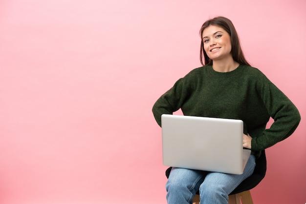 ピンクの背景に分離された彼女のラップトップで椅子に座っている若い白人女性が腰に腕を組んでポーズをとって、笑顔