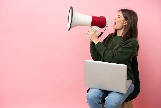 Молодая кавказская женщина сидит на стуле со своим ноутбуком, изолированным на розовом фоне, кричит в мегафон