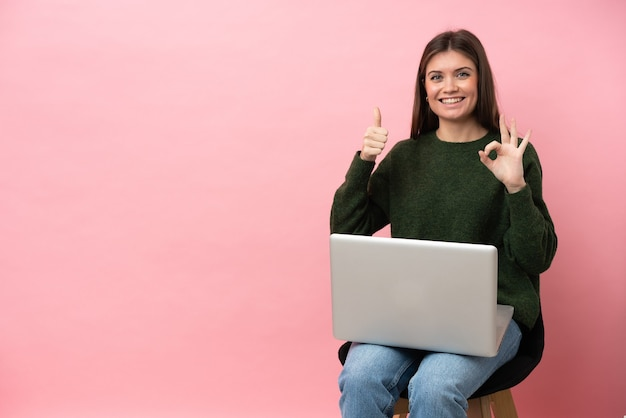 Молодая кавказская женщина, сидящая на стуле со своим ноутбуком, изолированным на розовом фоне, показывает знак ок и жест пальца вверх