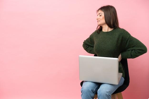 Молодая кавказская женщина, сидящая на стуле со своим ноутбуком, изолированным на розовом фоне, страдает от боли в спине из-за того, что приложила усилия