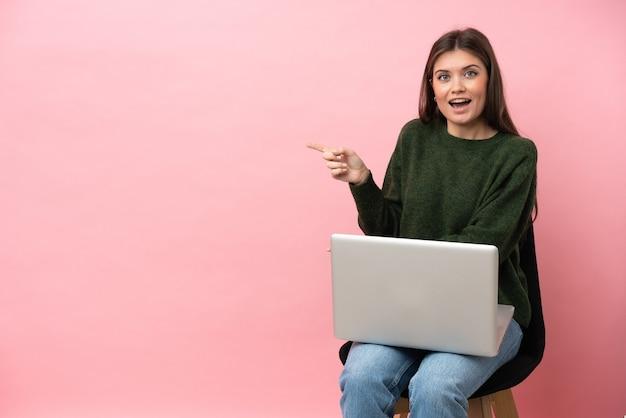 Молодая кавказская женщина, сидящая на стуле со своим ноутбуком, изолированным на розовом фоне, удивлена и указывает сторону