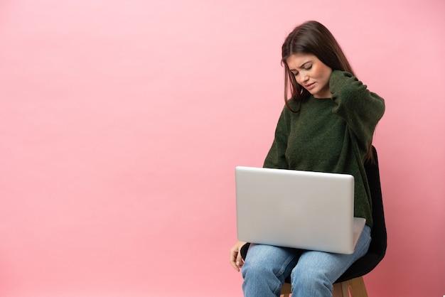 목에 통증이 있는 분홍색 배경에 격리된 노트북을 들고 의자에 앉아 있는 젊은 백인 여성