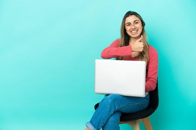 Молодая кавказская женщина сидит на стуле со своим компьютером, изолированным на синем фоне, показывает палец вверх жестом