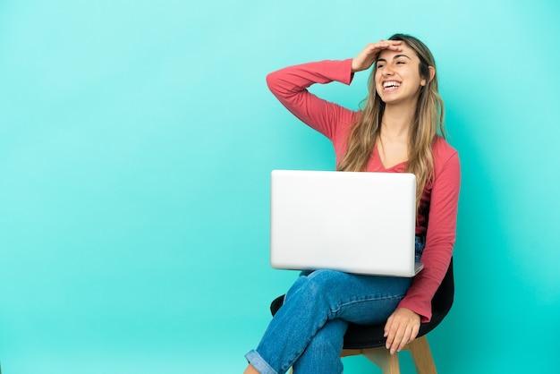 파란색 배경에 고립 된 그녀의 pc와 함께 의자에 앉아 젊은 백인 여자는 뭔가를 실현하고 해결책을 계획하고 있습니다
