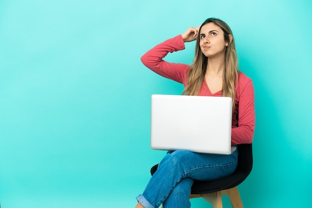 의심을 가지고 혼란스러운 얼굴 표정으로 파란색 배경에 고립 된 그녀의 pc와 함께 의자에 앉아 젊은 백인 여자
