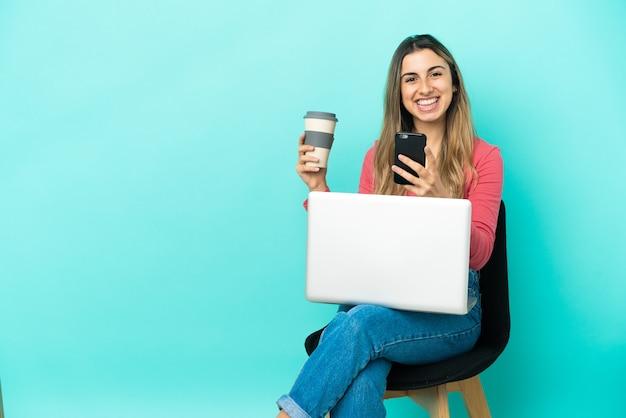 Молодая кавказская женщина сидит на стуле со своим компьютером, изолированным на синем фоне, держит кофе на вынос и мобильный