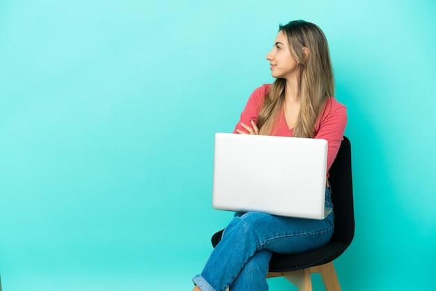 Молодая кавказская женщина сидит на стуле со своим компьютером, изолированным на синем фоне в боковом положении