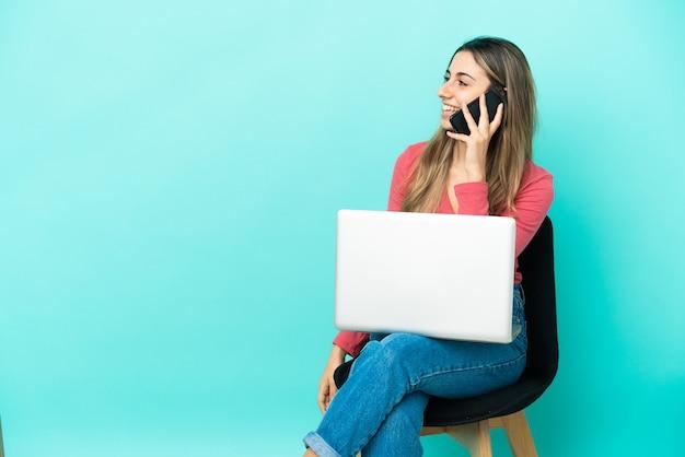 누군가와 휴대 전화로 대화를 유지하는 파란색 배경에 고립 된 그녀의 pc와 함께 의자에 앉아 젊은 백인 여자