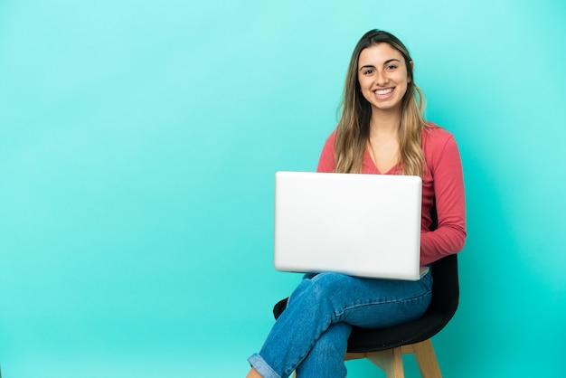 Молодая кавказская женщина сидит на стуле со своим компьютером, изолированным на синем фоне, смеясь