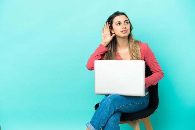 Молодая кавказская женщина сидит на стуле со своим компьютером, изолированным на синем фоне, слушая что-то, положив руку на ухо
