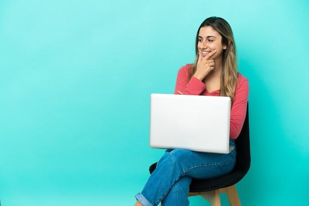 Молодая кавказская женщина сидит на стуле со своим компьютером, изолированным на синем фоне, глядя в сторону