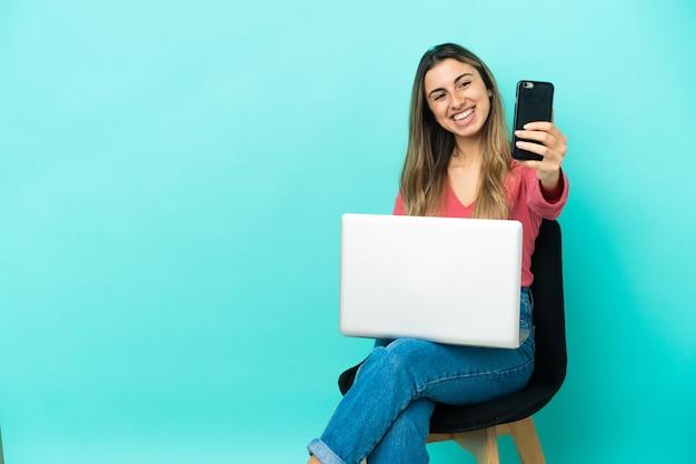 Молодая кавказская женщина сидит на стуле со своим компьютером, изолированным на синем фоне, делая селфи