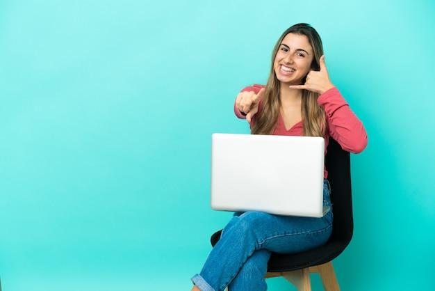 전화 제스처를 만들고 앞을 가리키는 파란색 배경에 고립 된 그녀의 pc와 함께 의자에 앉아 젊은 백인 여자