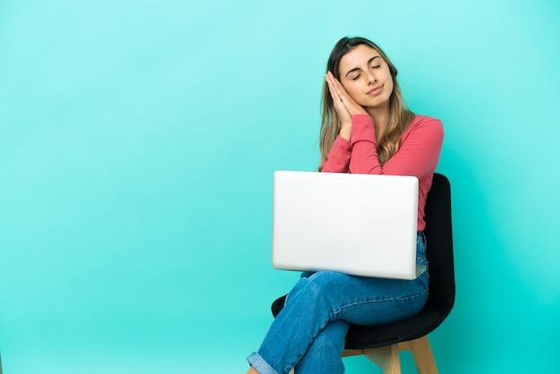 그녀의 pc와 함께 의자에 앉아 젊은 백인 여자는 dorable 식에서 수면 제스처를 만드는 파란색 배경에 고립