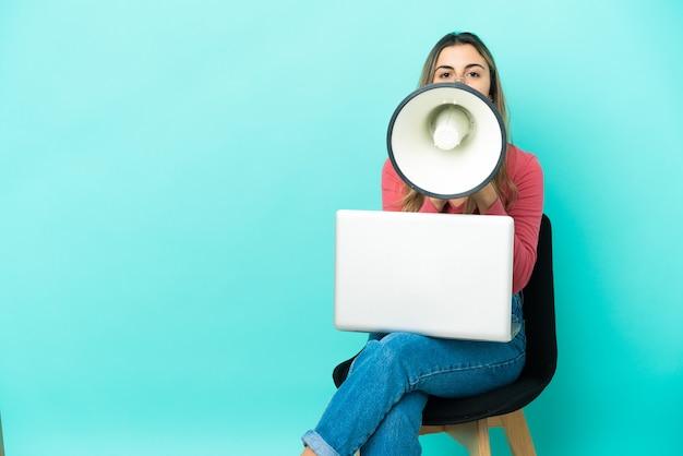 Молодая кавказская женщина сидит на стуле со своим компьютером, изолированным на синем фоне, кричит в мегафон