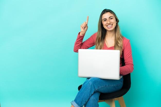 파란색 배경에 고립 된 그녀의 pc와 함께 의자에 앉아 젊은 백인 여자는 최고의 기호에 손가락을 들고