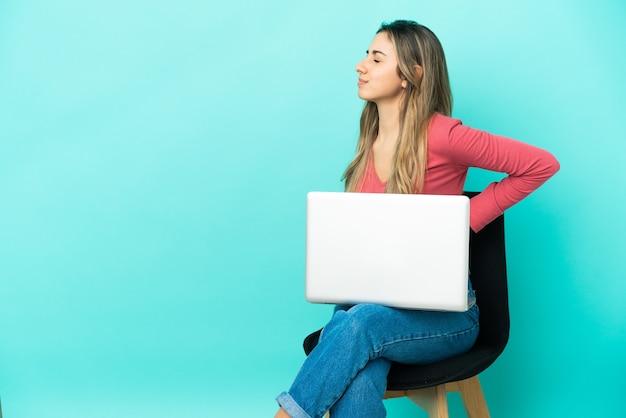 Молодая кавказская женщина сидит на стуле со своим компьютером, изолированным на синем фоне, страдает от боли в спине из-за того, что приложила усилия