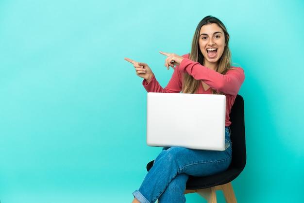파란색 배경에 놀란과 가리키는 측면에 고립 된 그녀의 pc와 함께 의자에 앉아 젊은 백인 여자