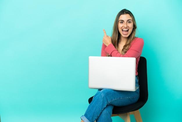Молодая кавказская женщина, сидящая на стуле со своим компьютером, изолированным на синем фоне, удивлена и указывает сторону
