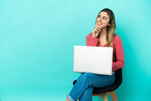 Молодая кавказская женщина сидит на стуле со своим компьютером, изолированным на синем фоне, думая об идее, глядя вверх