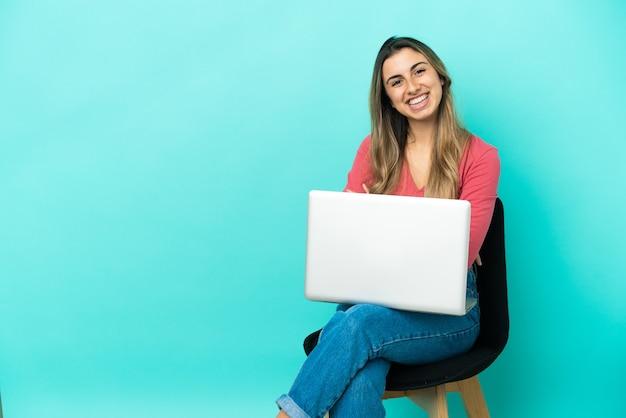 Молодая кавказская женщина сидит на стуле со своим компьютером, изолированным на синем фоне, со скрещенными руками и с нетерпением ждет