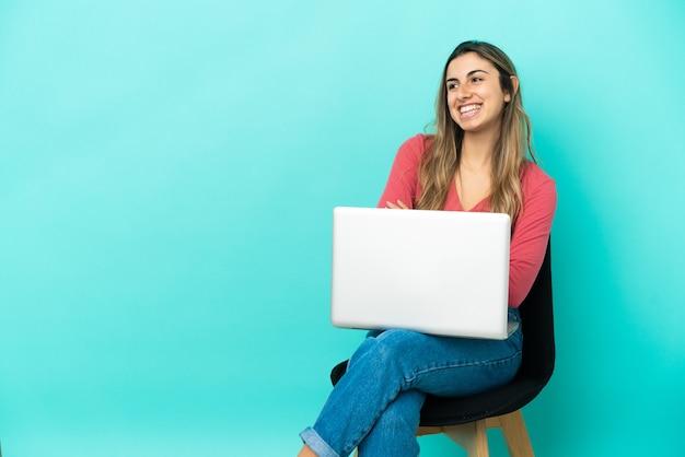 Молодая кавказская женщина сидит на стуле с изолированным компьютером