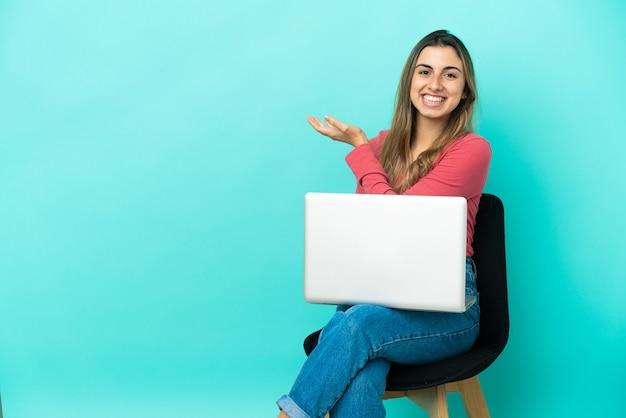 Молодая кавказская женщина сидит на стуле с изолированным компьютером Premium Фотографии