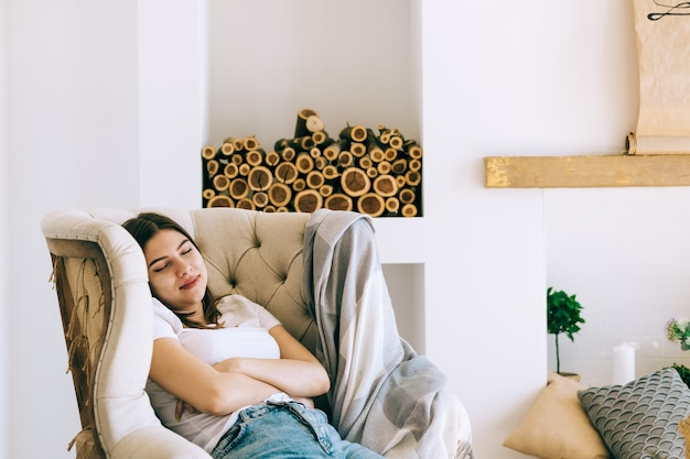 Молодая кавказская женщина, сидящая на кресле в гостиной, спит после тяжелого рабочего дня, вздремнет или помечтит
