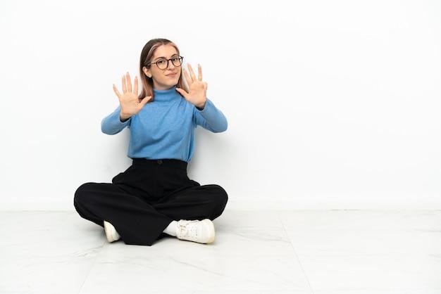 Молодая кавказская женщина, сидящая на полу, считая девять пальцами