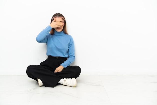 手で目を覆って床に座っている若い白人女性。何かを見たくない