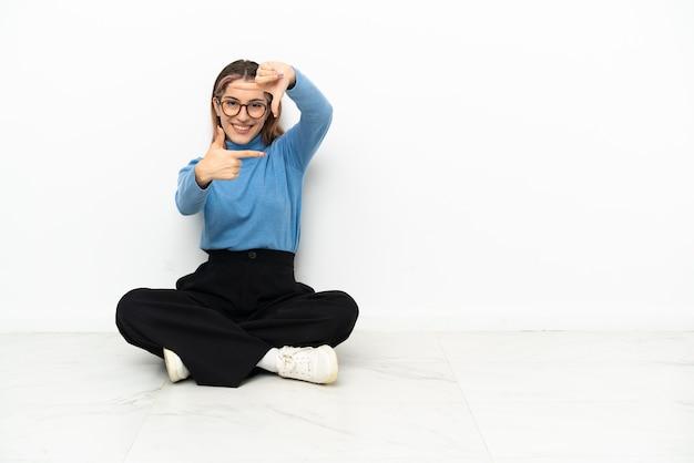 顔に焦点を当てて床に座っている若い白人女性。フレーミングシンボル