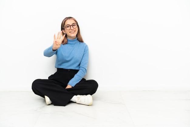 幸せな床に座って、指で4を数える若い白人女性