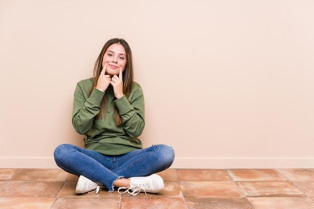 Молодая кавказская женщина, сидящая на полу, изолировала сомнения между двумя вариантами.