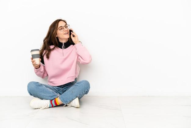 Молодая кавказская женщина сидит на полу, изолированном на белом фоне, держит кофе на вынос и мобильный