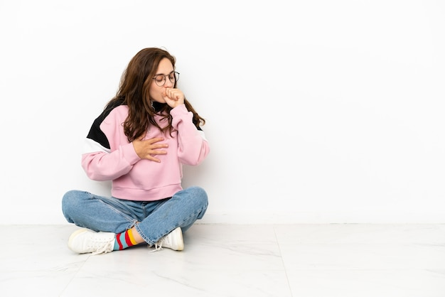 흰색 배경에 격리된 바닥에 앉아 있는 젊은 백인 여성은 기침을 하고 기분이 나쁩니다