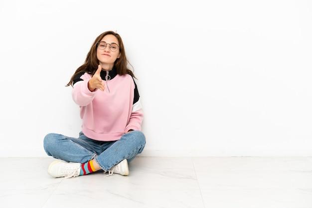 Молодая кавказская женщина сидит на полу на белом фоне, пожимая руку для заключения хорошей сделки