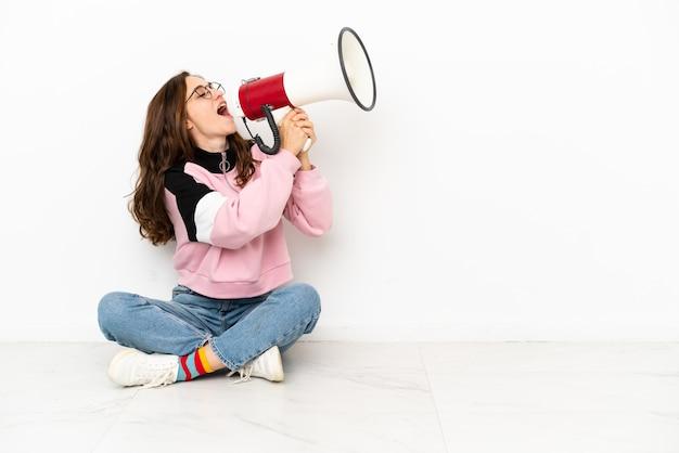 Молодая кавказская женщина сидит на полу, изолированном на белом фоне, кричит в мегафон